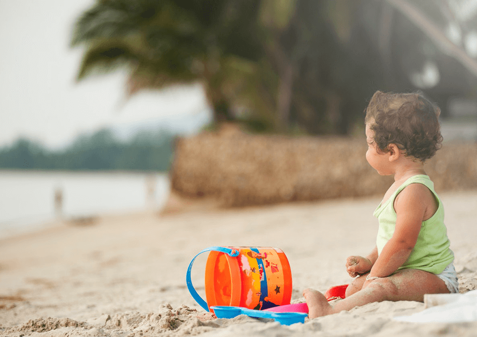 baby standing next to the beach